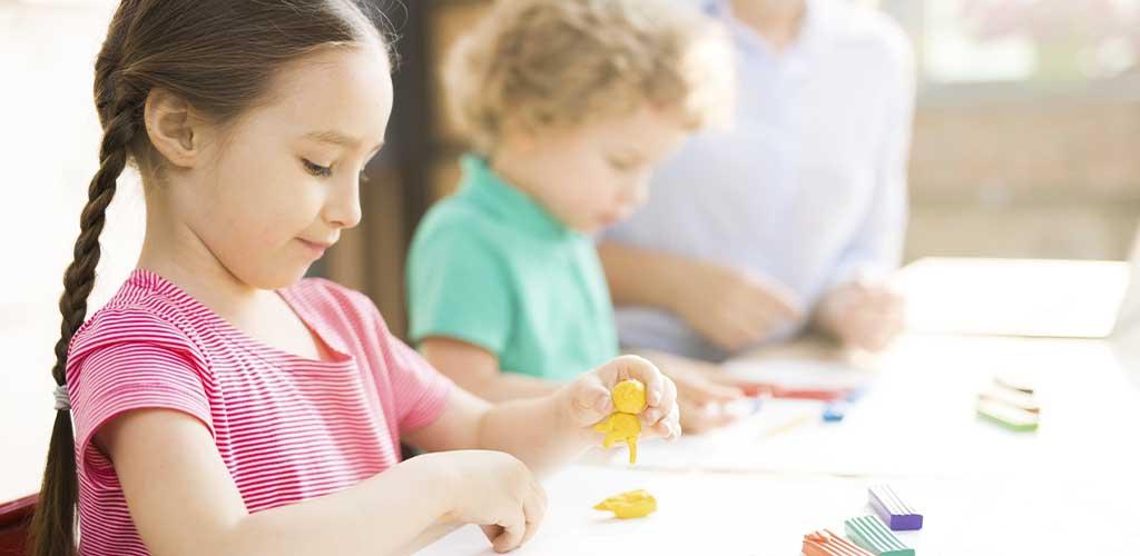 niños jugando con plastilina en casa